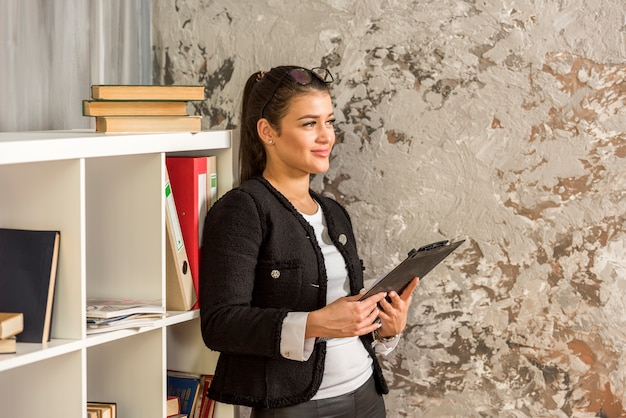 Brunette businesswoman using her tablet Free Photo