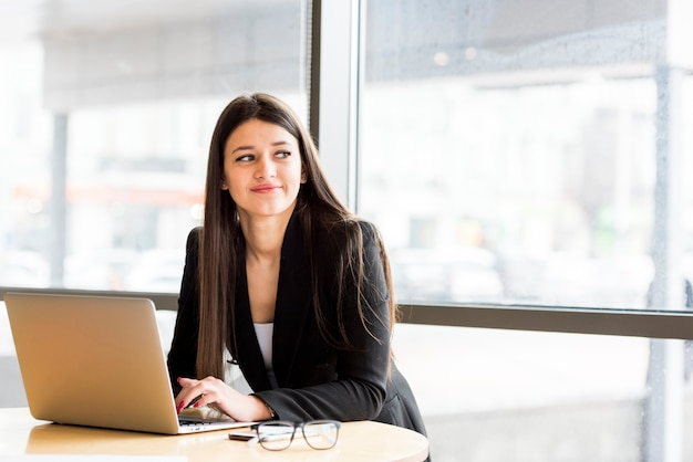 Brunette businesswoman with laptop Free Photo