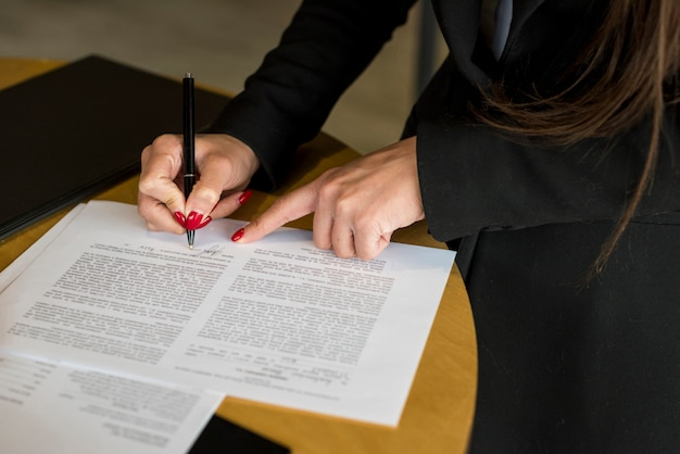 Brunette businesswoman writing on a document Free Photo