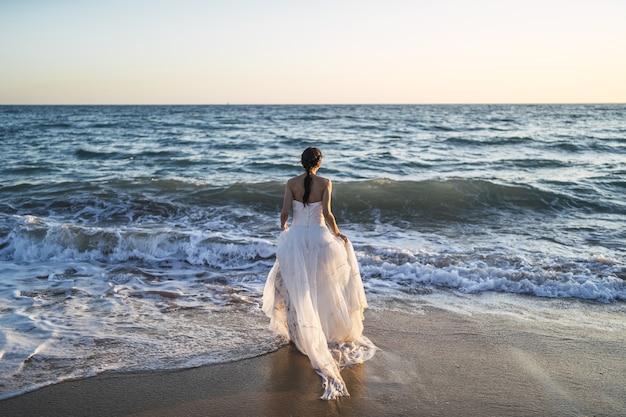 하얀 웨딩 드레스에 바다에 접근하는 갈색 머리 백인 신부 무료 사진