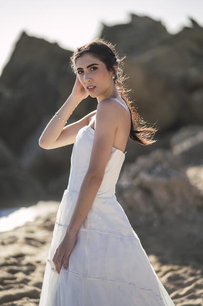 해변에서 결혼식 동안 포즈를 취하는 갈색 머리 백인 신부 무료 사진
