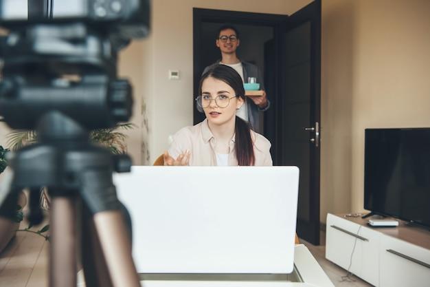 Брюнетка кавказская дама проводит онлайн-урок, ожидая, пока муж принесет ей завтрак Premium Фотографии