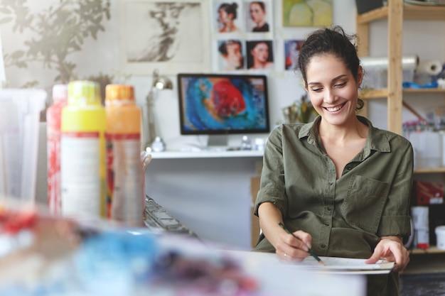 캐주얼 옷에 갈색 머리 귀여운 여성, 즐거운 표정, 연필과 빈 골판지 잡고, 영감과 좋은 분위기를 유지하면서 스케치 만들기, 워크샵 또는 직장에 있음 무료 사진