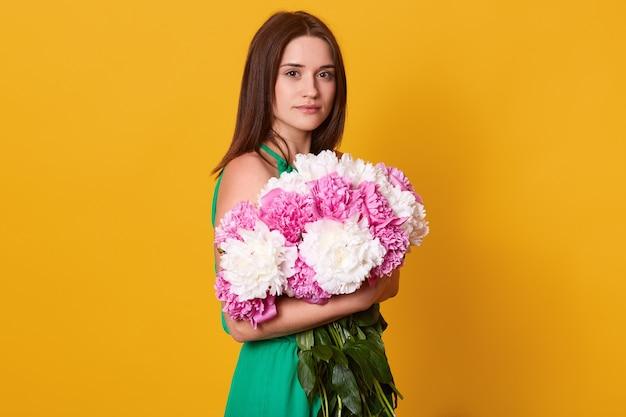 Брюнетка женщина обнимает большой букет с розовыми и белыми пионами, стильная женщина с цветами, имеет спокойное выражение лица, позирует изолированные на желтом. Бесплатные Фотографии