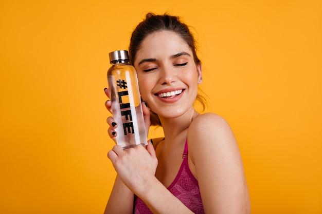 Signora bruna fitness sorridente con gli occhi chiusi Foto Gratuite