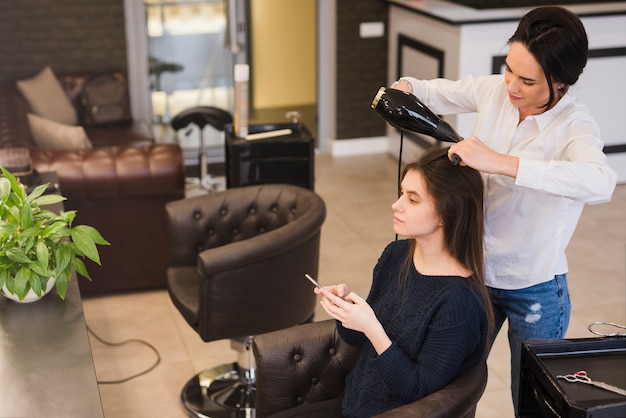 Brunette girl getting her hair done Free Photo