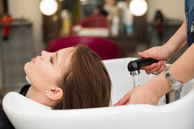 Brunette girl getting her hair washed Free Photo