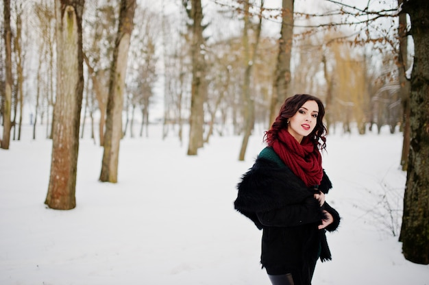 Brunette girl in green sweater, coat and red scarf outdoor on evening winter day. Premium Photo