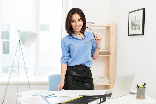 Девушка брюнетка в голубой рубашке и черной юбке стоит возле стола в офисе. она держит в руке очки и улыбается в камеру. Бесплатные Фотографии