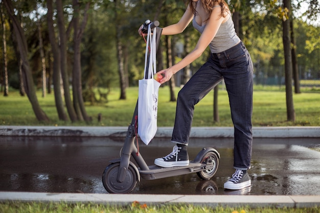 A brunette girl is standing next to electric scooter in the park and takes an apple from a bag Premium Photo