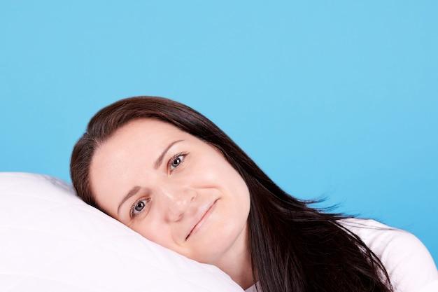 Брюнетка девушка легла на белую подушку и улыбнулась. изолированные на синем фоне. Premium Фотографии