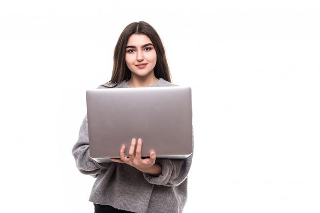 Брюнетка девушка модель в сером свитере стоит и работает studie на своем ноутбуке Бесплатные Фотографии