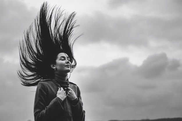 Brunette girl outdoor with blowing up hair Premium Photo
