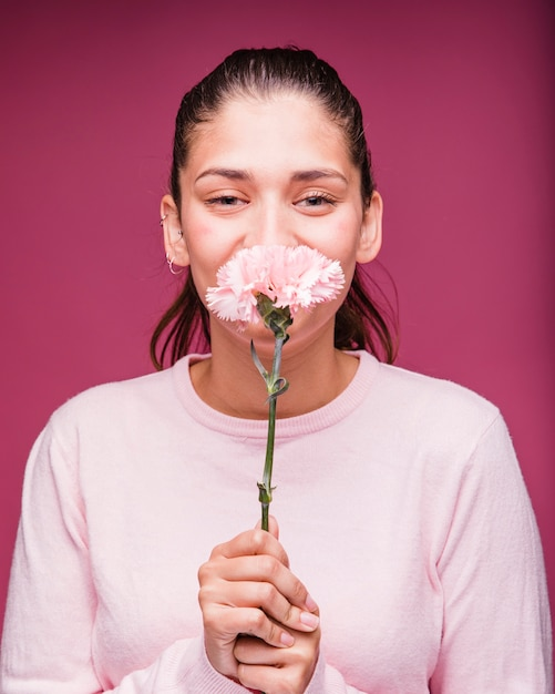 Brunette girl posing with carnation Free Photo