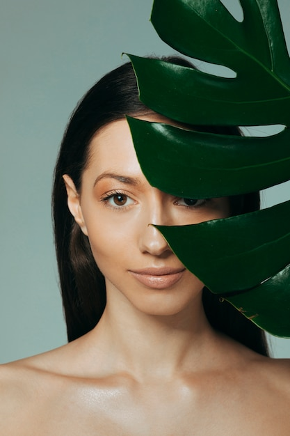 Brunette girl posing with exotic leaves Free Photo
