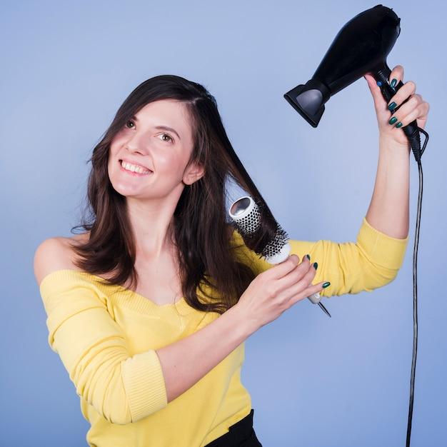 Brunette girl posing with hair dryer Free Photo