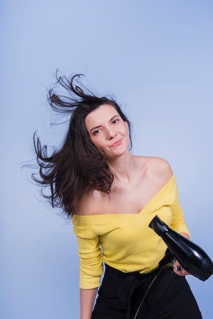 Brunette girl posing with hair dryer Free Photo