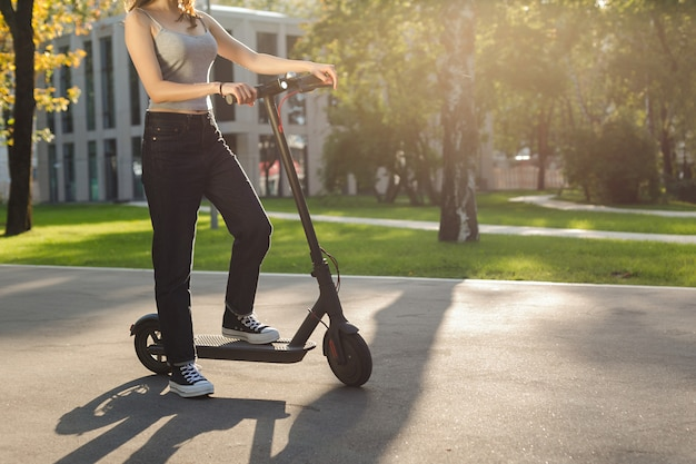 Brunette girl riding an ecofriendly electric kick scooter in a park in sunny weather on sidewalks Premium Photo