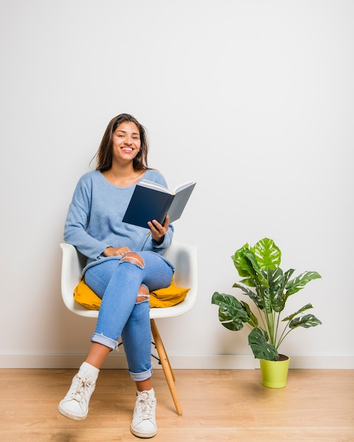 Brunette girl sitting reading a book Free Photo