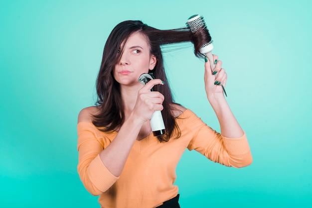 Brunette girl taking care of her hair Free Photo