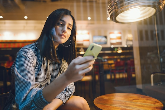 Brunette girl using her cellphone to reach a friend Free Photo