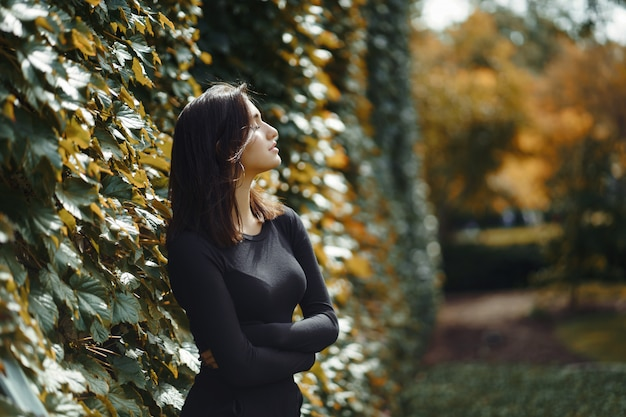 Brunette girl walking through the park during autumn Free Photo