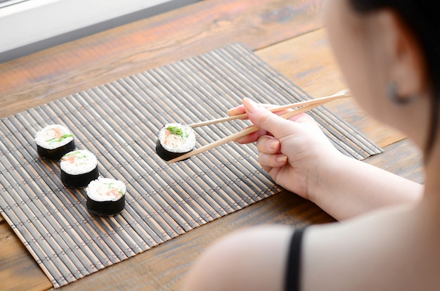 Brunette girl with chopsticks holds a sushi roll on a bamboo straw serwing mat background Premium Photo