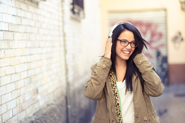 Brunette girl with glasses listening to music with headphones Free Photo