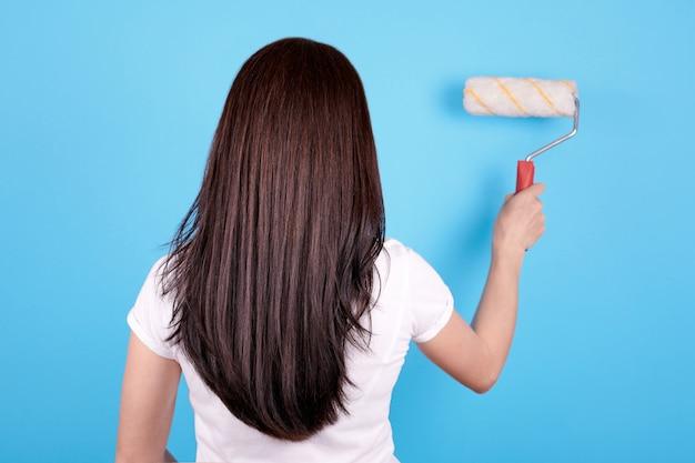 ペイントローラーを使用して長い髪のブルネットの少女、後ろから表示します。青色の背景に分離されました。 Premium写真