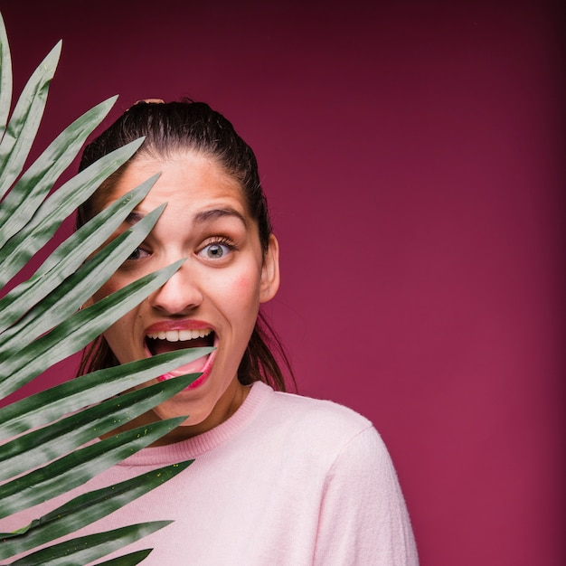 Brunette girl with tropical leaf Free Photo