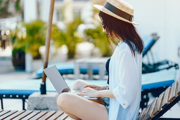 Brunette girl working on her computer by the pool Free Photo
