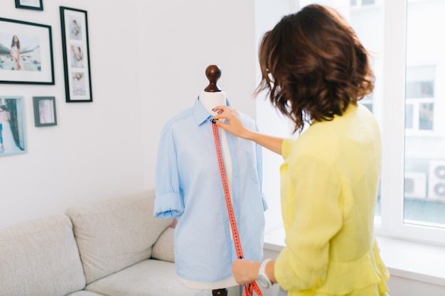 Brunette girl in a yellow jacket  makes  fitting shirt on mannequin. she works in a large workshop studio. the picture shows a view from the back. Free Photo