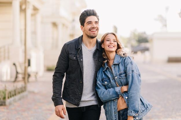 주말에 여자 친구와 함께 걷는 갈색 머리 남자. 데이트를 즐기는 행복 한 젊은 사람들의 야외 초상화. 무료 사진