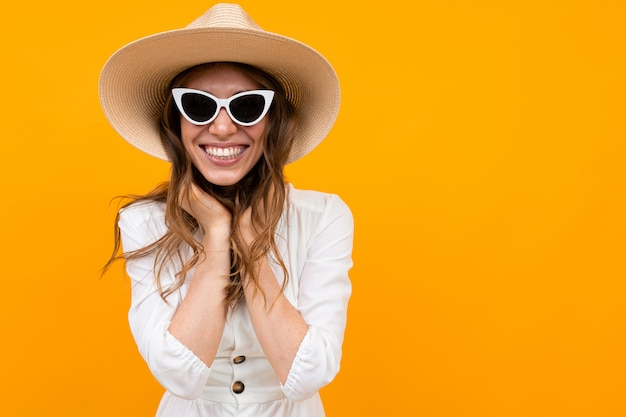 Brunette in a hat and sunglasses on a  of a yellow wall, half-length portrait Premium Photo
