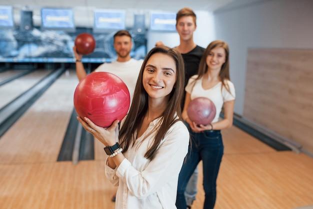 Brunette è felice di essere lì. i giovani amici allegri si divertono al bowling durante i fine settimana Foto Gratuite