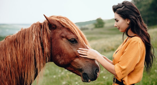 Brunette lady touching her brown horse while posing in a field near forest Premium Photo