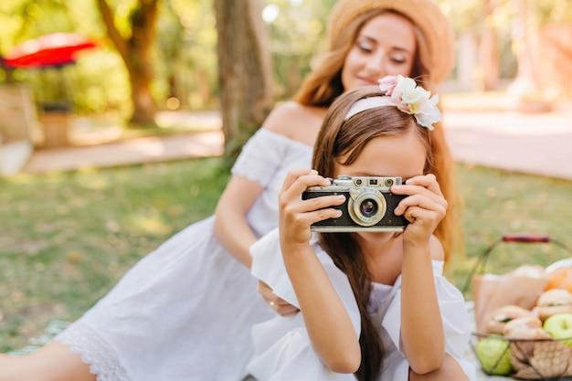 週末を楽しんでいる自然の写真を撮る髪のリボンとブルネットの少女。彼女の娘がカメラを持っている公園で魅力的な若い女性の屋外の肖像画。 無料写真