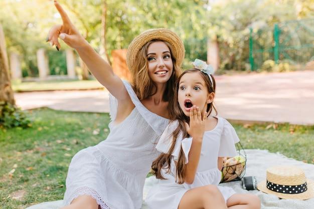 自然にショックを受けた表情でポーズをとるブルネットの長い髪の子供。白い服とヴィンテージの帽子をかぶった見事な若い女性は、何か面白いものを見て、指で指しています。 無料写真