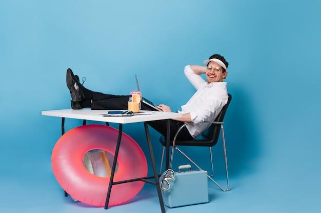 Bruna uomo in giacca e cravatta sta lavorando mentre ci si rilassa con un cocktail sullo spazio blu con valigia e anello di gomma rosa. Foto Gratuite