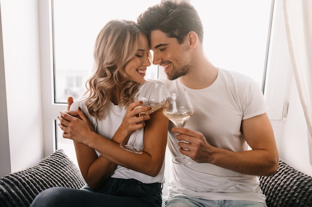 Uomo castana che abbraccia la ragazza e beve champagne. coppia di famiglia che celebra anniversario. Foto Gratuite