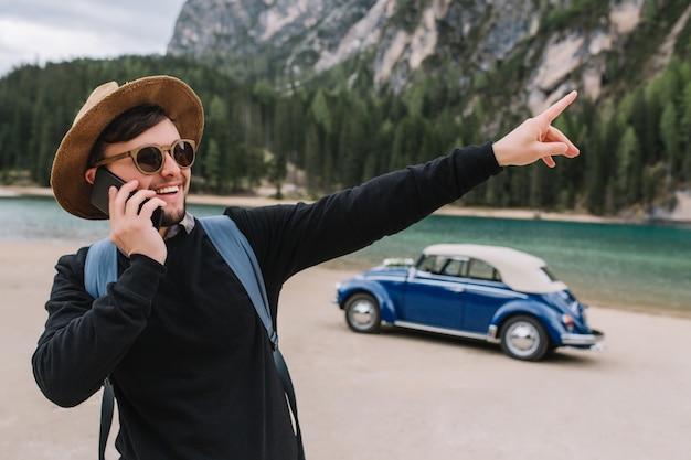 ブルネットの男は、川岸に沿って散歩中に電話で話し、何か面白いものに人差し指でサングラスと黒いスウェットシャツを着ています 無料写真