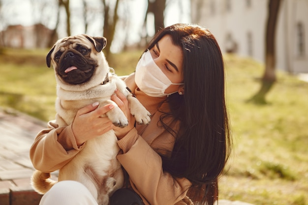 Brunette in a mask walks with pug Free Photo