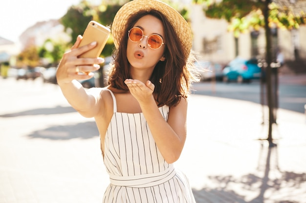 Brunette model in summer clothes posing on the street using mobile phone giving air kiss Free Photo