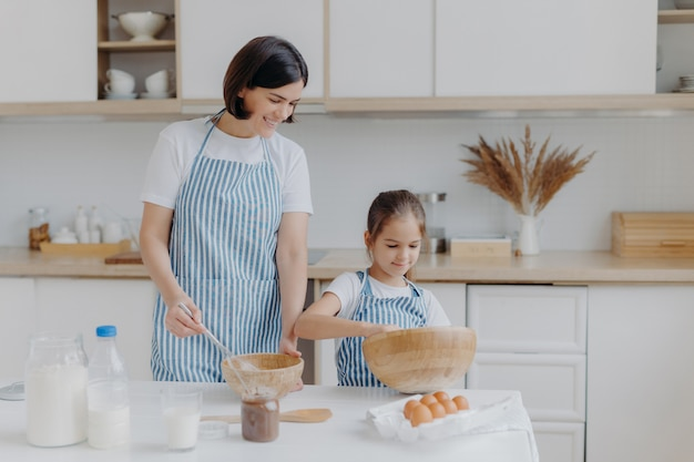 Brunette mother and little kid make cookie dough Premium Photo