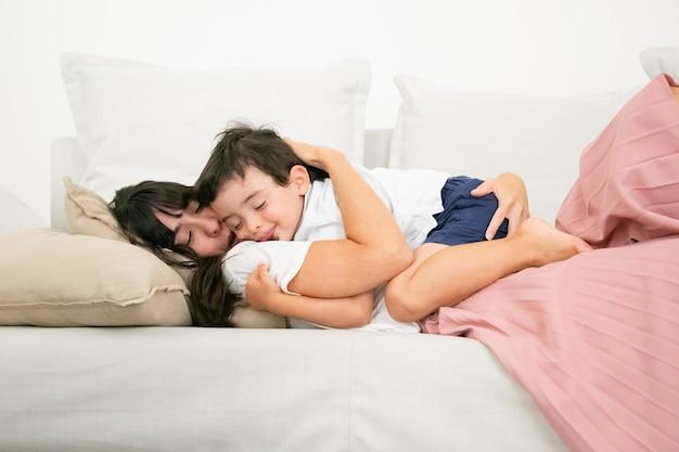 ソファで寝ているとかわいい息子を抱きしめるブルネットの母。 無料写真