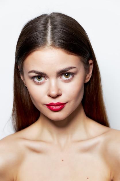 Брюнетка обнаженные плечи привлекательный взгляд красные губы очаровывают прозрачную кожу Premium Фотографии