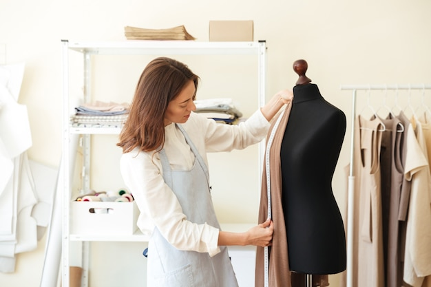 Brunette seamstress in apron measuring beautiful fabric on black dummy in workshop Free Photo