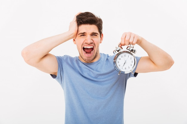 Brunette sleepy young man 30s holding alarm clock and yawning after sleepless night, isolated over white wall Premium Photo