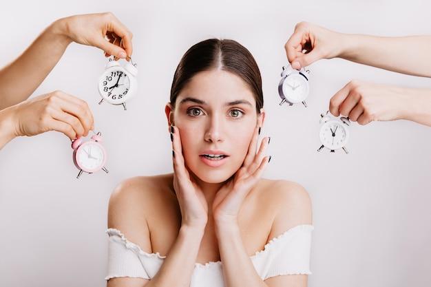 Bruna in top bianco chiude le orecchie dal campanello d'allarme. ritratto di ragazza con gli occhi verdi sul muro bianco. Foto Gratuite