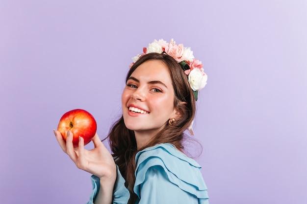 彼女の髪にバラのブルネットは赤いリンゴを保持しています。現代の白雪姫をイメージした女の子のクローズアップの肖像画。 無料写真